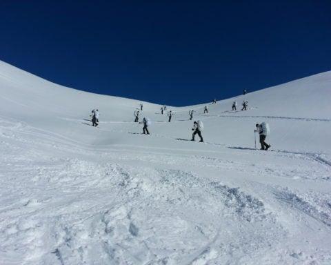 Legionnaires climbing on snowy montain
